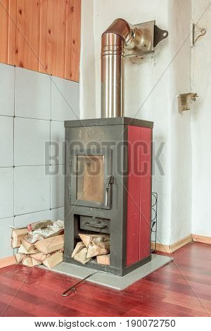 Traditional rustic metal stove and stacked firewood