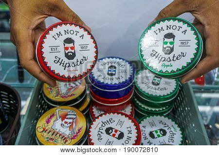 Labuan,Malaysia-May 26,2017:Man's hand holding the various kind of hair styling gel oil pomade at street market in Labuan,Malaysia.Pomade gives the user's hair a shiny & slick appearance.