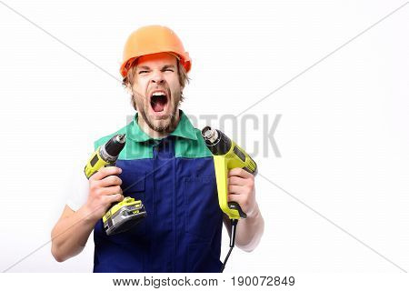 Brutal working man shouts and holds yellow building tools in hands wears green blue uniform and orange helmet isolated on white background. Hard work concept