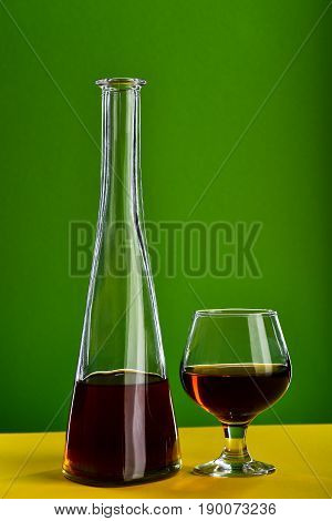 Glass with brandy near bottle in shape of cone standing on yellow surface on green background