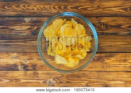 Glass bowl with crisps on wooden table, top view