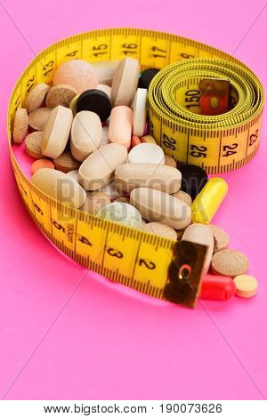 Concept Of Health, Diet And Calories: Measuring Tape And Pills