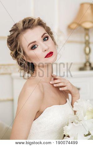 Sensual portrait of bride blonde in a white interior