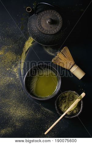 Green tea matcha powder and hot drink in black bowls standing with iron teapot, bamboo traditional tools spoon and whisk over dark metal background. Top view with space
