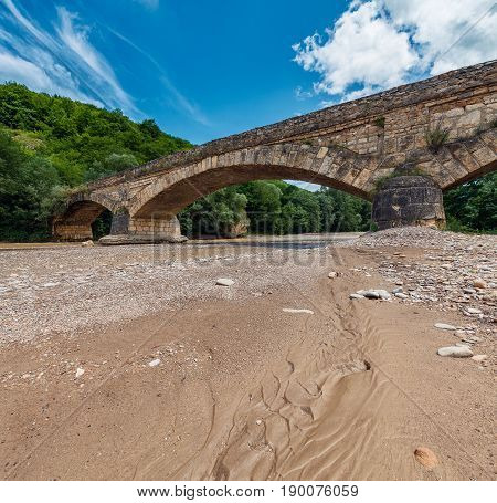Old stone bridge across the shallow dried at summer river with sand banks