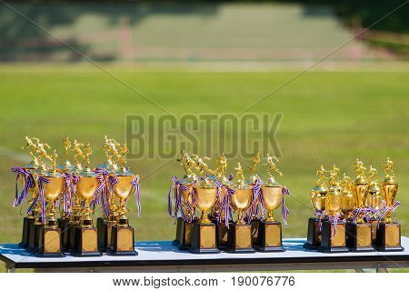 track and field trophies set up outdoor on table waiting for winners blurred grass field background with room for copy space on top