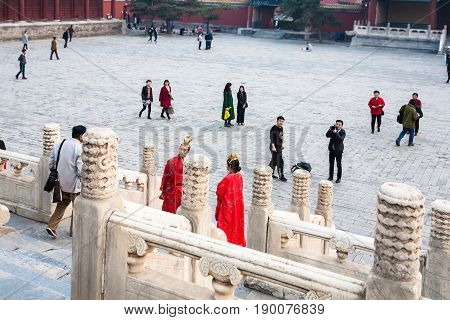 Couple In Red Dresses And People On Courtyard