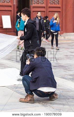 Photographer And Tourists On Courtyard In Beijing