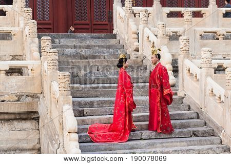 Couple In Chinese Dresses On Steps Of Temple