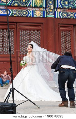 Photographer And Bride On Courtyard Of Temple