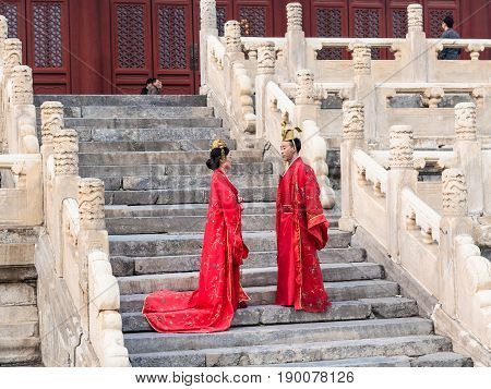 Couple In Traditional Costumes On Steps Of Temple