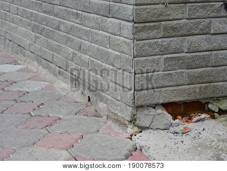 Close up on Foundation Repair - Warning Signs. House foundation repair.Broken Foundation House Brick Wall.