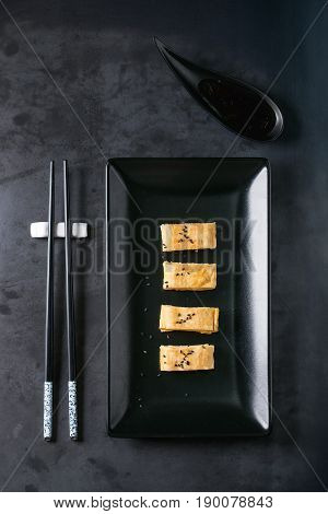 Japanese Rolled Omelet Tamagoyaki sliced with black seasame seeds and soy sauce, served in black square ceramic plate with chopsticks over dark metal background. Top view with space