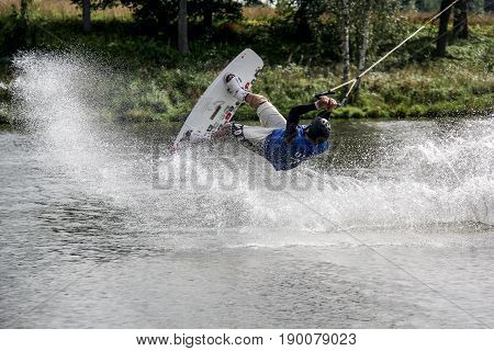 Man is among a splash of water he is riding a wakeboard  and jumping upside down