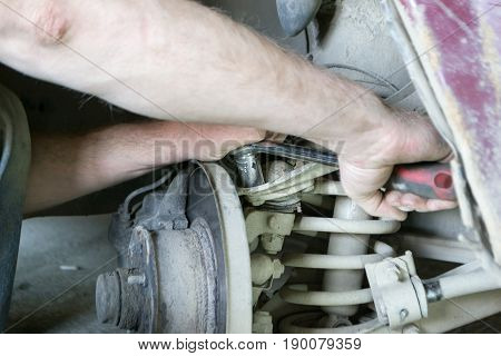A professional mechanic repairs the car. Tighten the bolt.