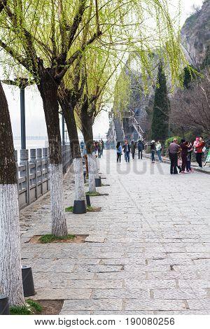 People On Embankment Of Yi River In Longmen