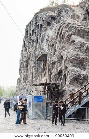 Visitors Near Carved Rocks In Longmen Grottoes