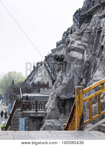 People And Carved Slope In Longmen Grottoes