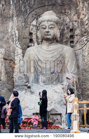 Visitors Near The Big Vairocana Statue In Longmen