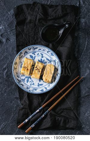 Japanese Rolled Omelet Tamagoyaki sliced with black seasame seeds and soy sauce, served in blue white ornate ceramic plate with chopsticks, textile over black stone background. Top view with space