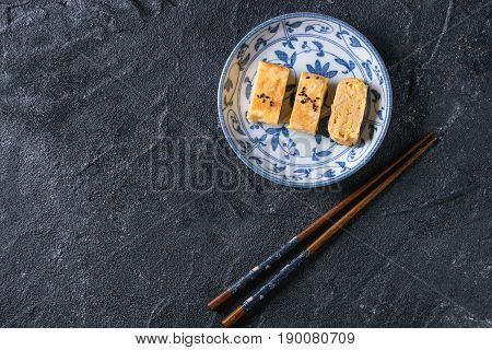 Japanese Rolled Omelette Tamagoyaki sliced with black seasame seeds and soy sauce, served in blue white ornate ceramic plate with chopsticks over black stone texture background. Top view with space