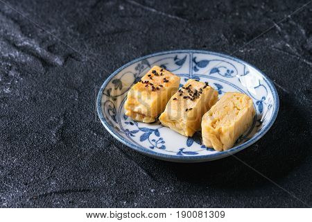 Japanese Rolled Omelet Tamagoyaki sliced with black seasame seeds and soy sauce, served in blue white ornate ceramic plate over black stone texture background. Top view with space
