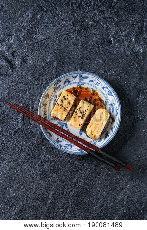 Japanese Rolled Omelette Tamagoyaki sliced with black sesame seeds and soy sauce, served in blue white ornate ceramic plate with chopsticks over black stone texture background. Top view with space