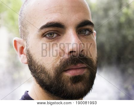 Portrait of a handsome, bald, young man with green eyes suddenly looking at the camera on the streets of Barcelona