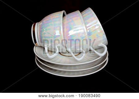 A pile of white iridescent tea cups and saucers