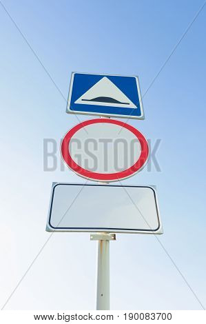Road signs under the blue sky on one column