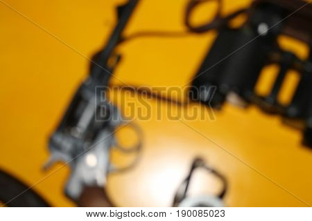 revolver, a hunting knife, binoculars and a compass on a yellow background, blurred background