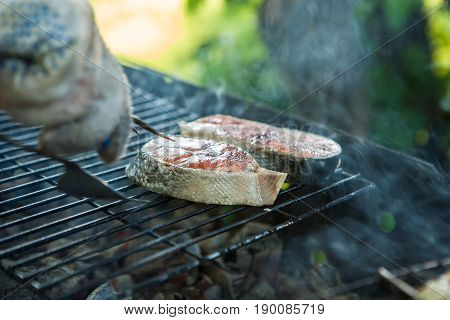 two pieces during cooking on the barbecue grill, salmon on the coals, a dish from the chef.