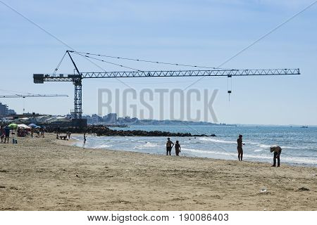 Constraction cranes on harbour with people on sandy beach in Summer