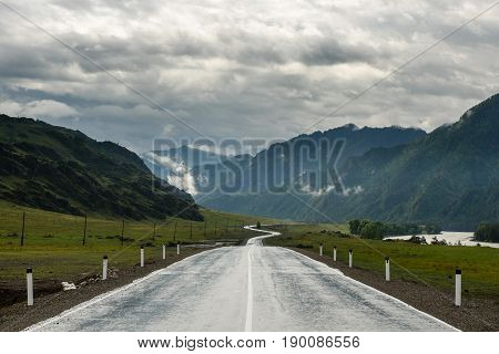 A winding road in the mountains in the valley of the river.