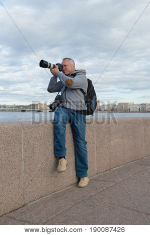 ST PETERSBURG, RUSSIA - MAY 03, 2017: The photographer shoots sitting on the parapet of Petrovskaya embankment