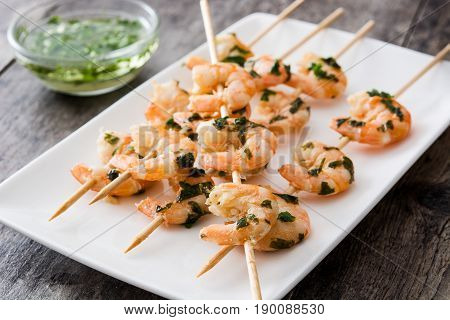 Delicious freshly shrimp skewers on wooden table