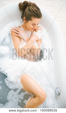 Young woman laying in bathtub with soapsuds