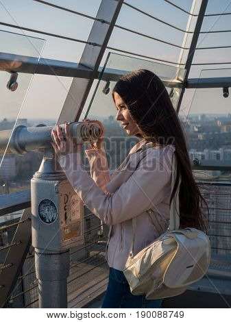 Tourist look observant binoculars telescope on panoramic view lifestyle concept trip traveler with backpack on background city