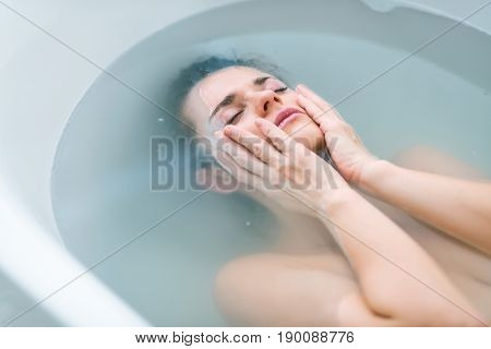 Frustrated young woman laying in water in bathtub