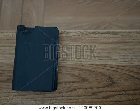 Holy Bible on old wooden church table top view