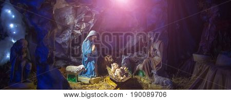 Nativity manger scene or crib with figurines of infant Jesus mother Mary Joseph sheep and magi in cave. Holy family. Christianity religion faith belief. Christmas holidays celebration