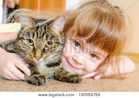 Sweet portrait of a cute little girl holding and snuggling kitten