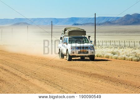 White pickup truck with roof tent is on an adventurous drive through the desert in Namibia. Speeding on a dusty road with a big cloud of dust.