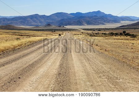 Adventurous drive on a rough gravel road through the desert towards the mountains. Straight and endless driving
