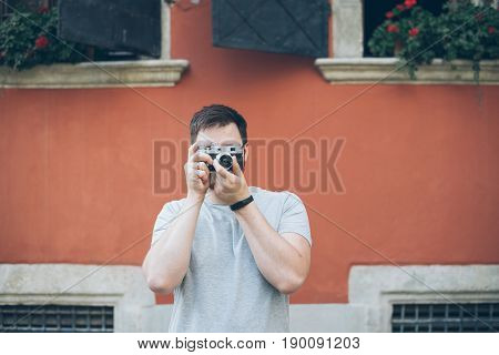 man shooting with old retro camera old building on background