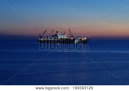 The ship that is laying a gas pipe on the sea bottom against the sunset