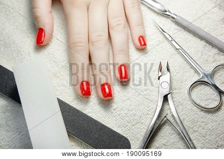 nail scissors file and clippers to remove the cuticle care products on white towel with woman manicured red nails