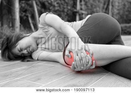 Asian woman runner touching her injured knee at outdoor - pain concept