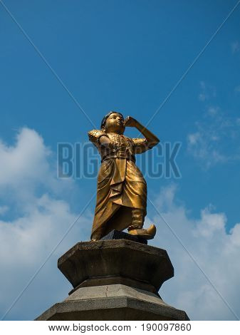 Gold statue and cloudy sunny sky background