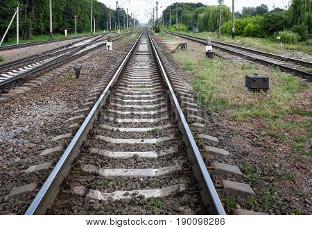 Summer. Three railway tracks go to the horizon. In the frame sleepers rubble stones poles green trees